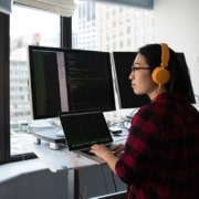 overcoming alert fatigue - employee in front of three computer screens looks out the window