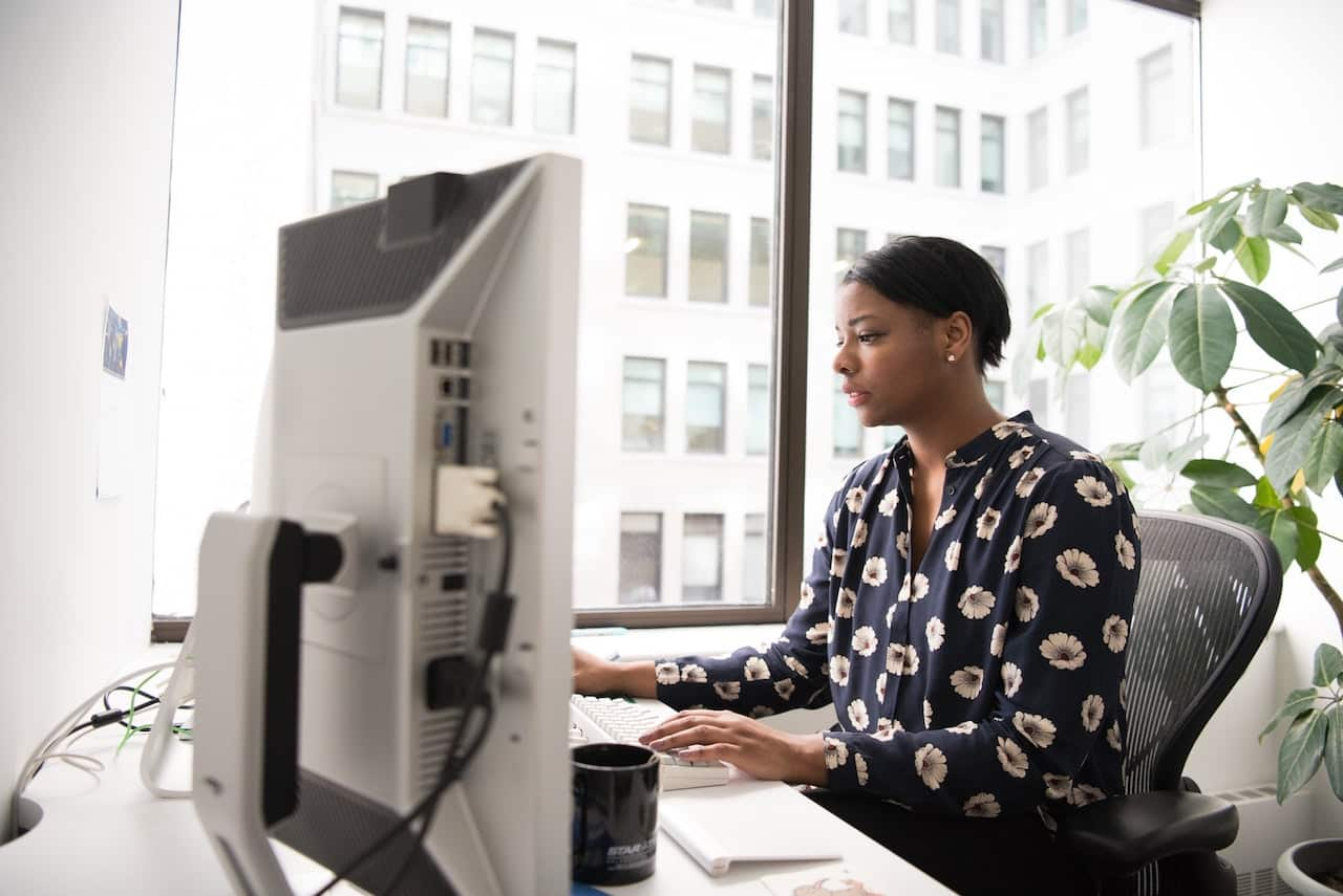 woman works at office computer to increase productivity and security through web filtering